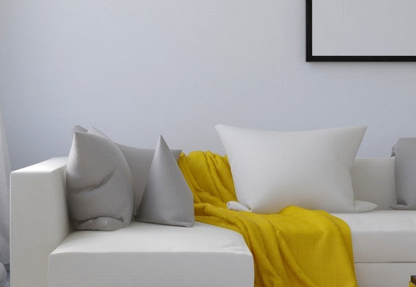 Yellow Throw Draped Over A White Faux Leather Sofa