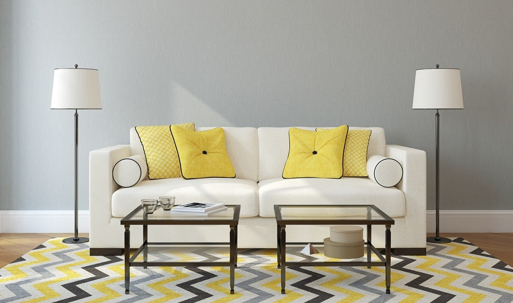 Grey And Yellow Geometric Rug, Under A Cream Sofa And In Front Of A Grey Wall