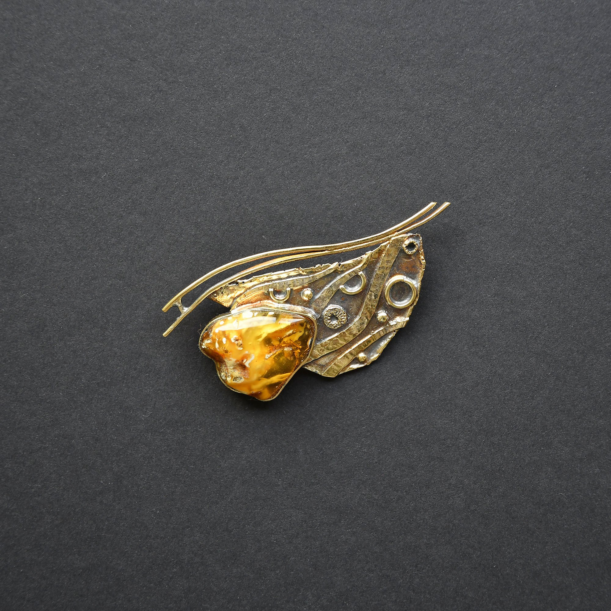 Brass brooch with a golden amber