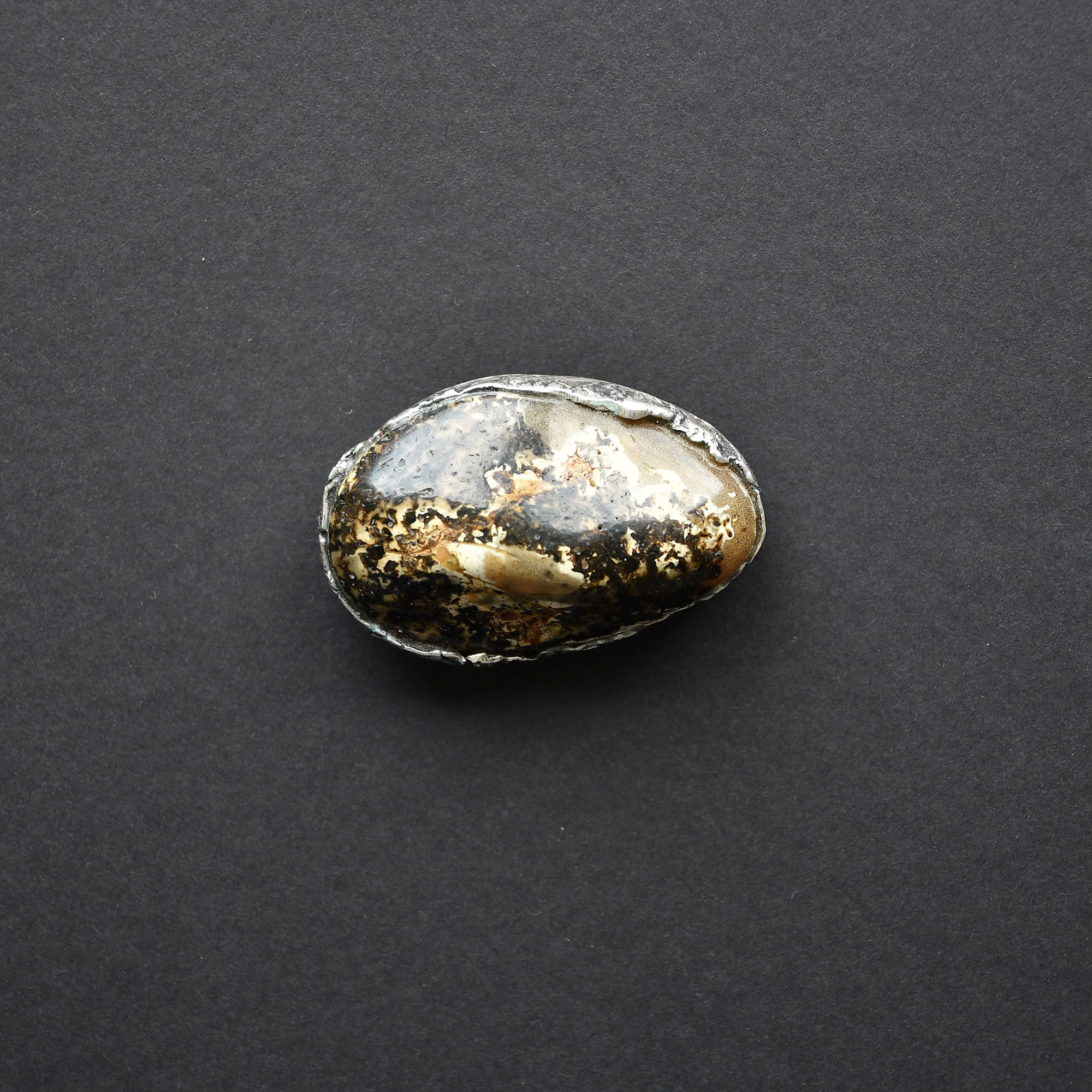 Brooch with black and white amber on a green background, set in silver