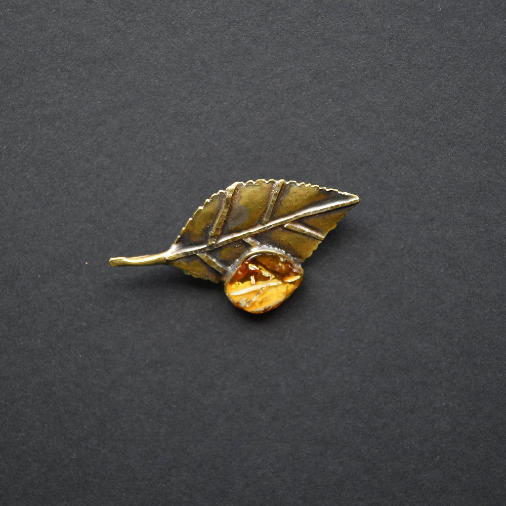 Brass brooch with a sunny amber