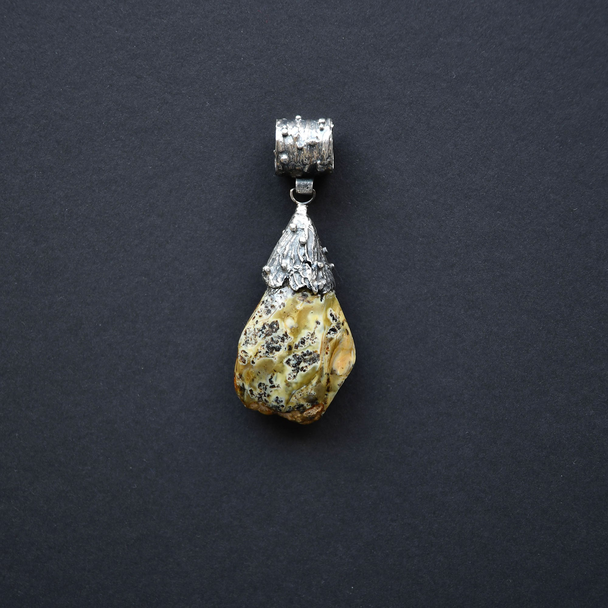 A drop-shaped green amber pendant with black and blue speckles