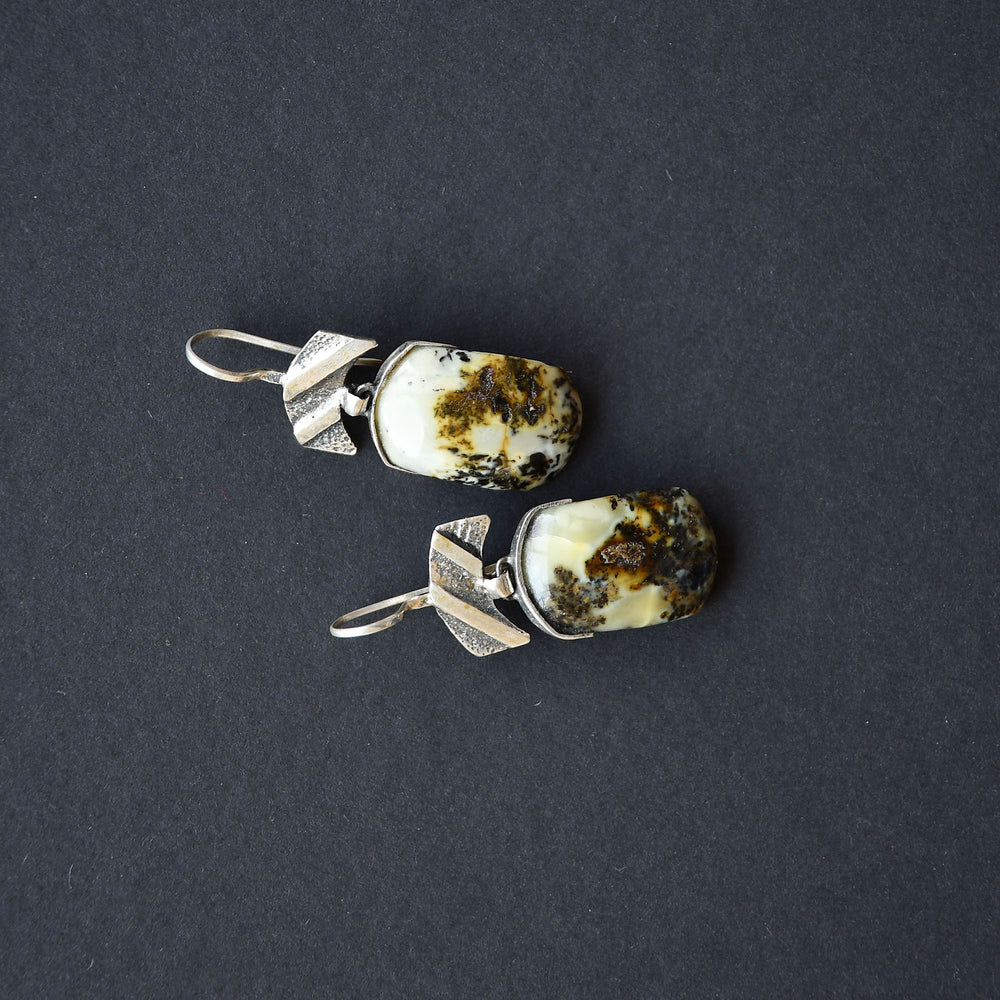 Earrings of green amber with speckles of black and blue patterns in silver setting
