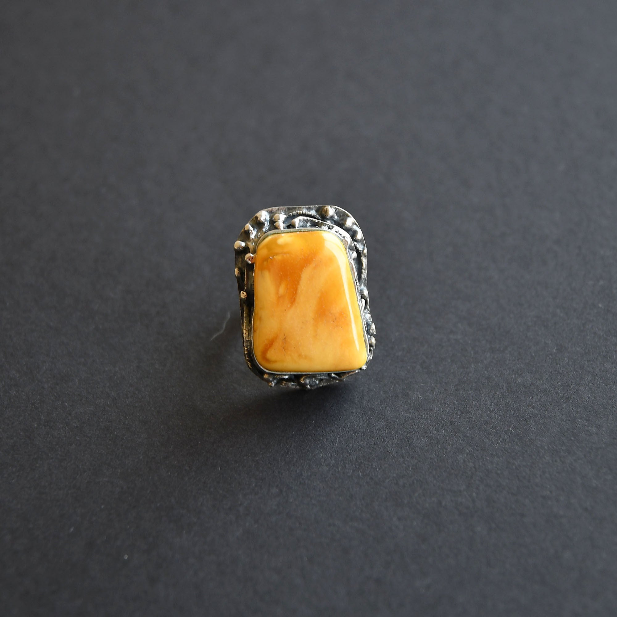 A ring with an old orange amber in silver setting
