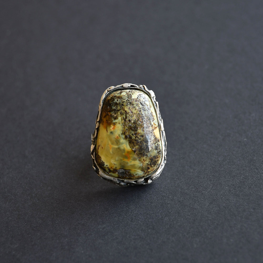 A ring with a landscape amber of green pattern in silver setting