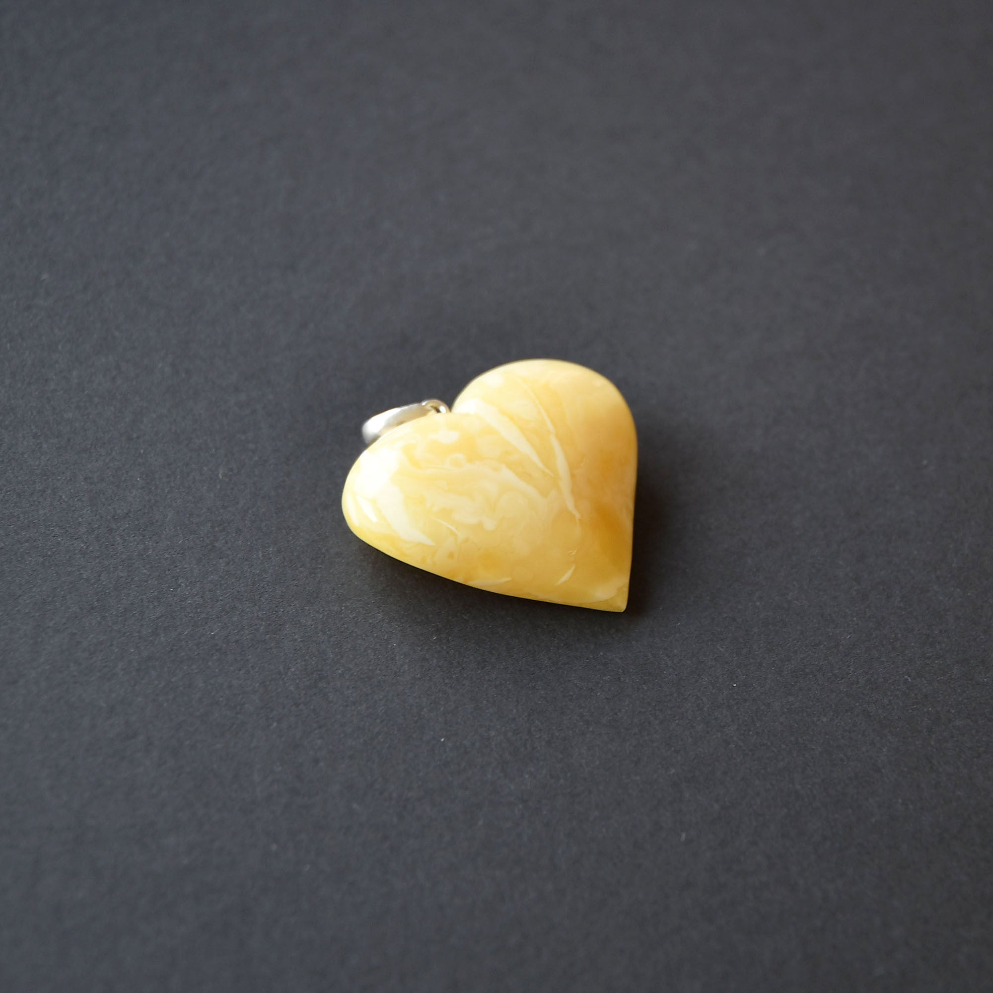 Amber heart of an amazingly white color amber with a pattern and silver loop