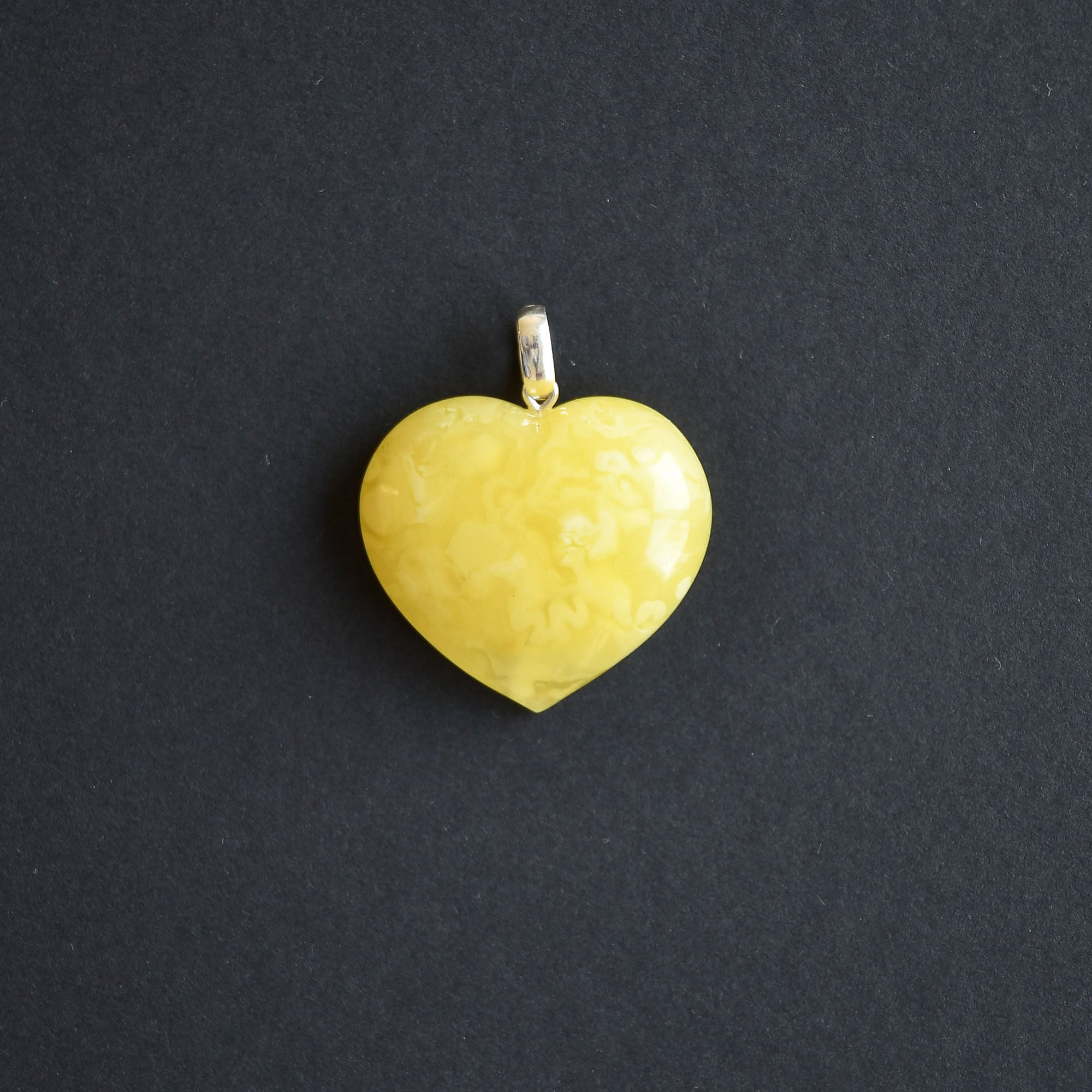 Amber heart of an unusual maize lemon colour with silver loop
