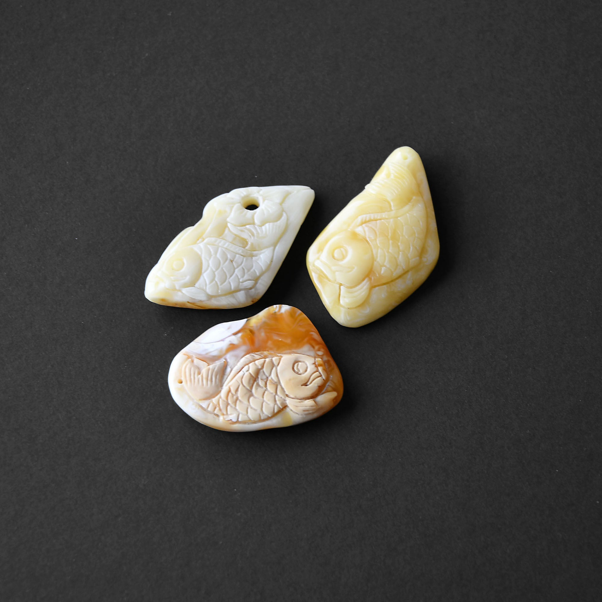 "Carved pendants of yellow and white amber ""Small fish"""