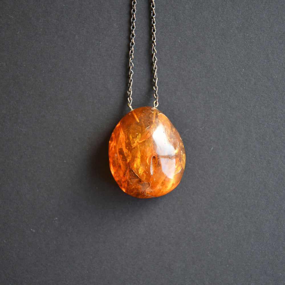 Vintage semi-transparent red amber pendant with vintage chain