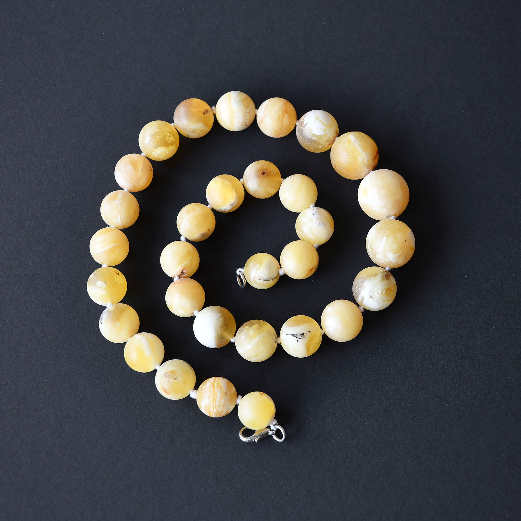 Round bead necklace of white unpolished amber and silver fastening