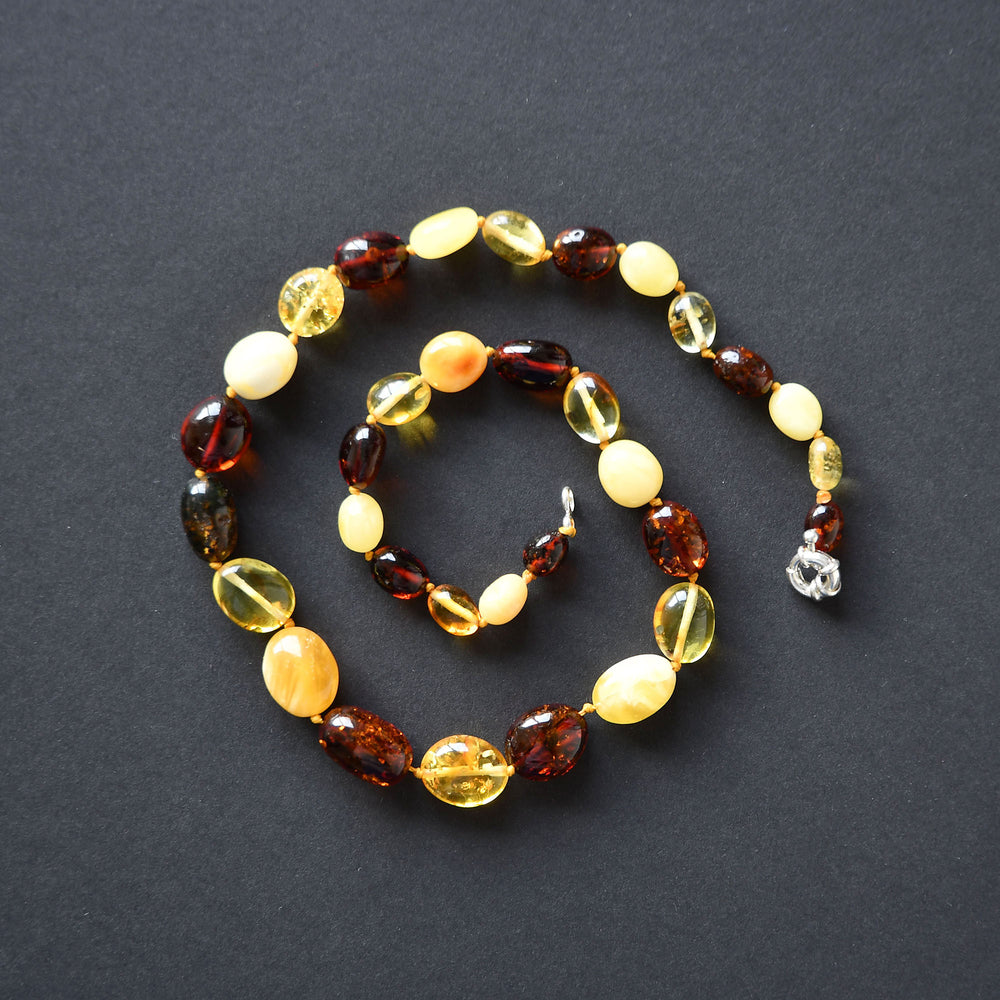 Colourful amber beads of oval form with a silver fastening