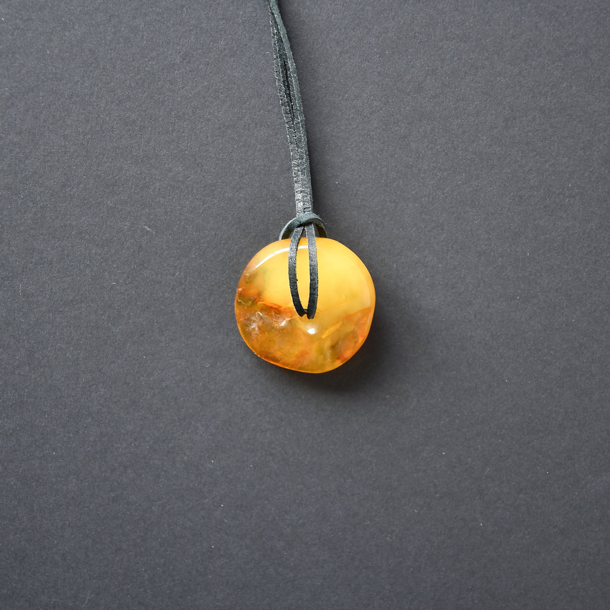 Yellow amber amulet of round form and a hole in the middle