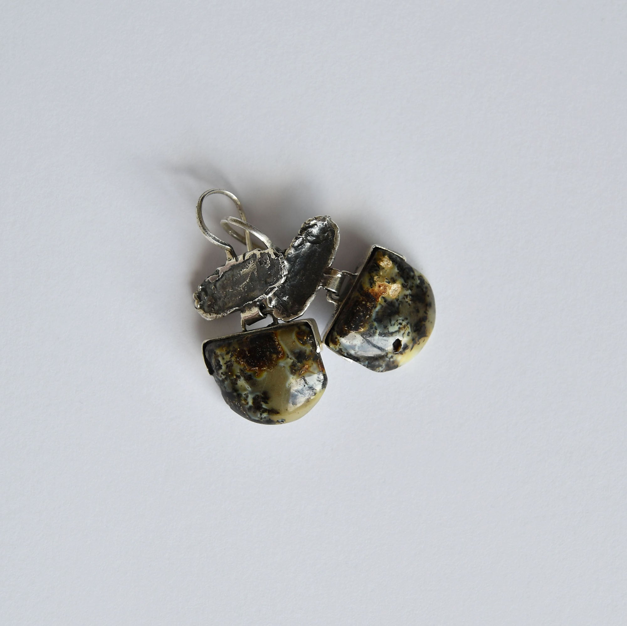 Black amber earrings with green and blue patterns in silver setting