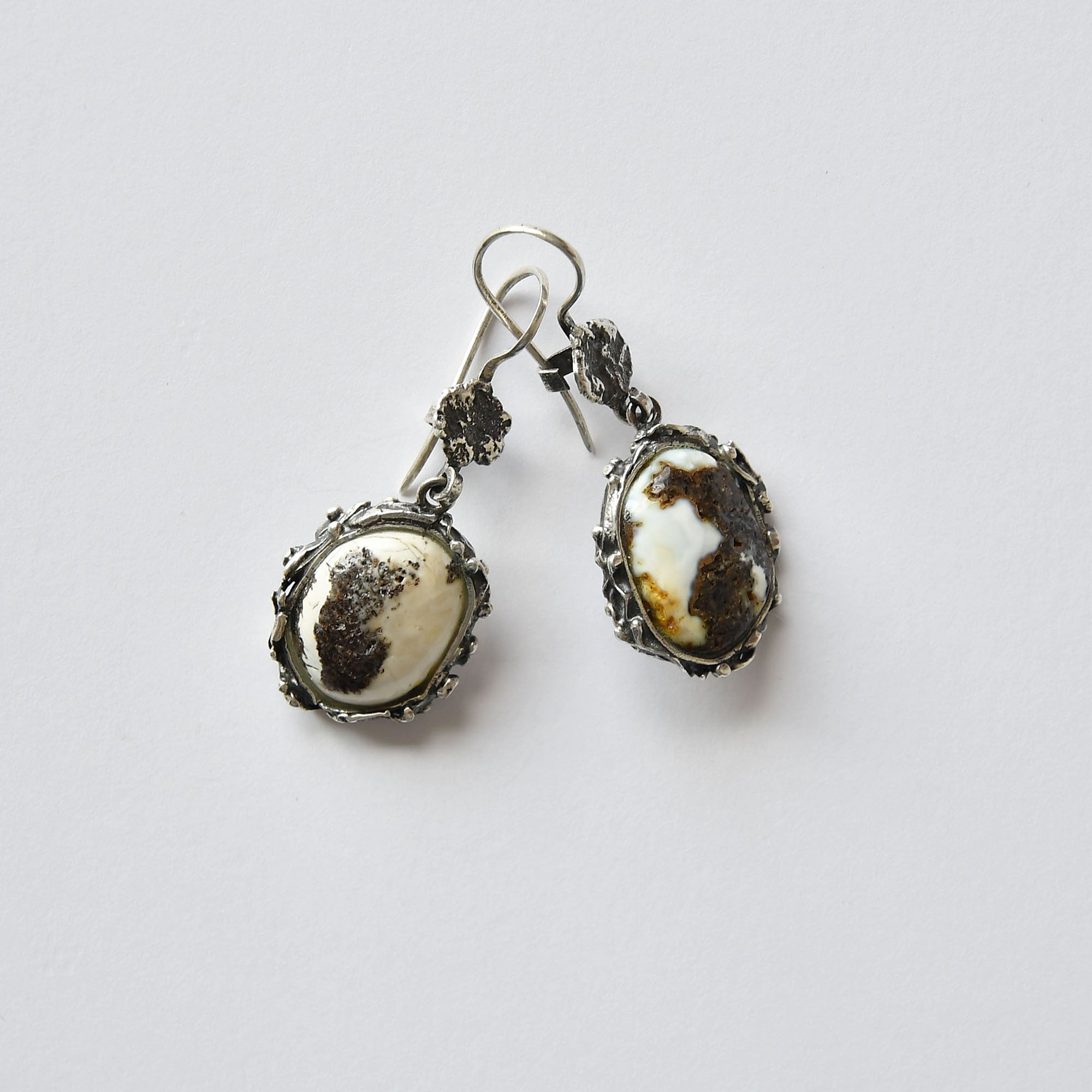 Oval earrings of white and black amber in silver setting