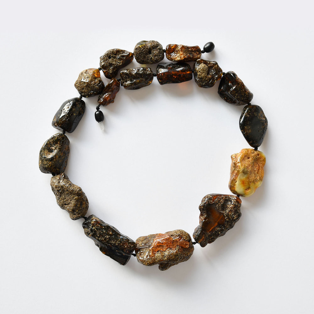Bead necklace of dark and black unpolished earthy amber