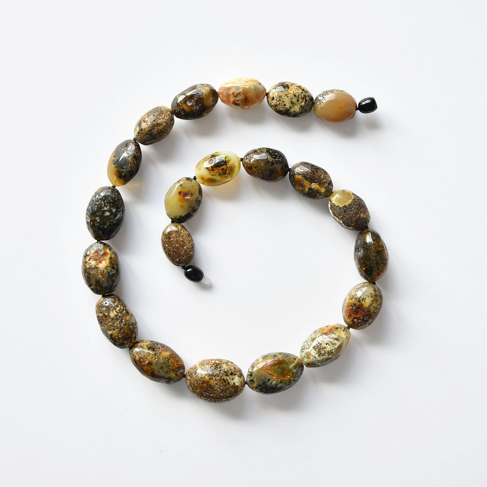 Beads of earthy amber of various patterns and olive form