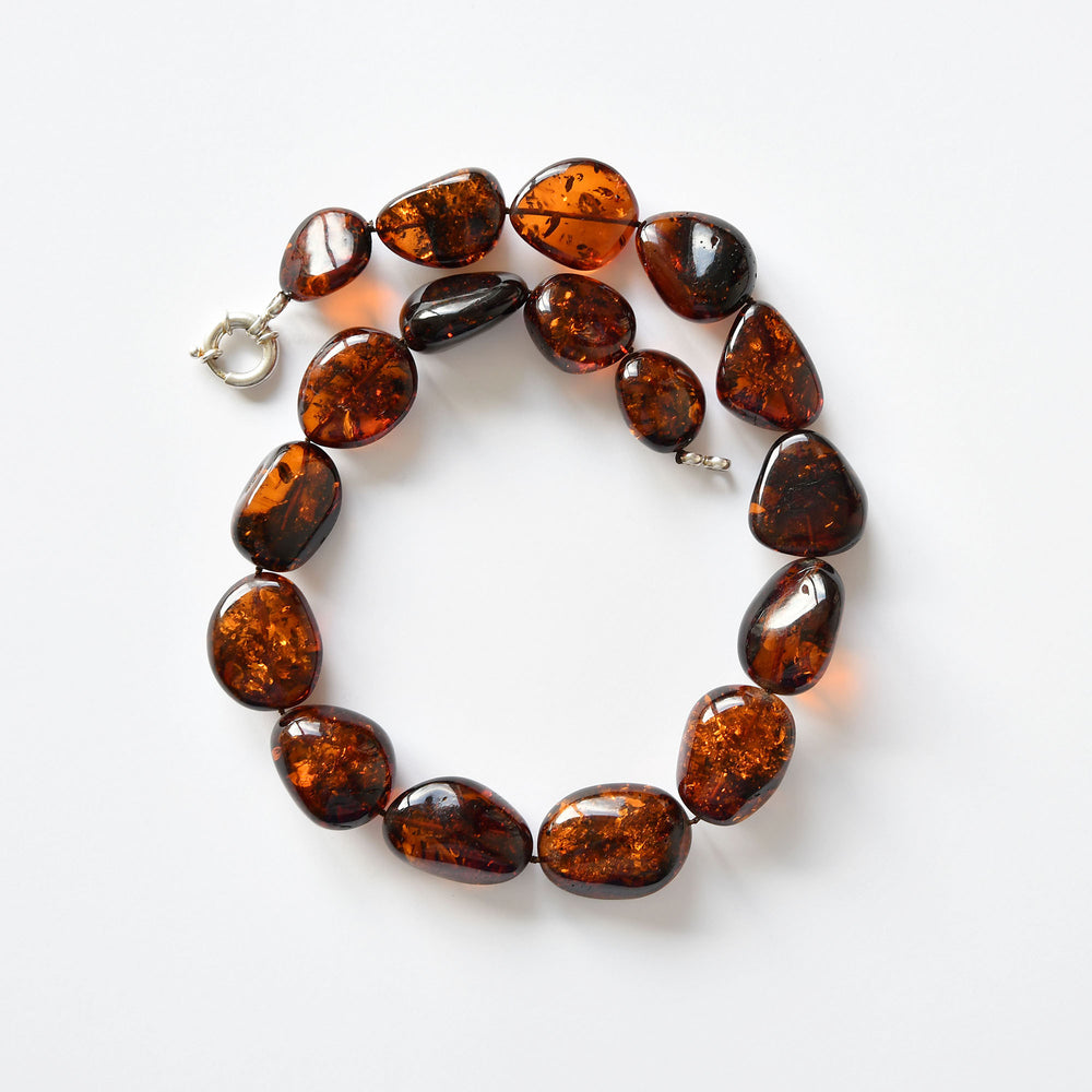 Round amber beads of the color of black tea with a silver fastening