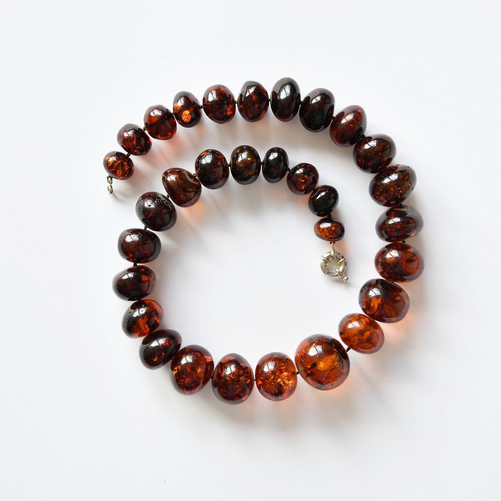 mber beads of dark cherry colour and round form with a silver fastening
