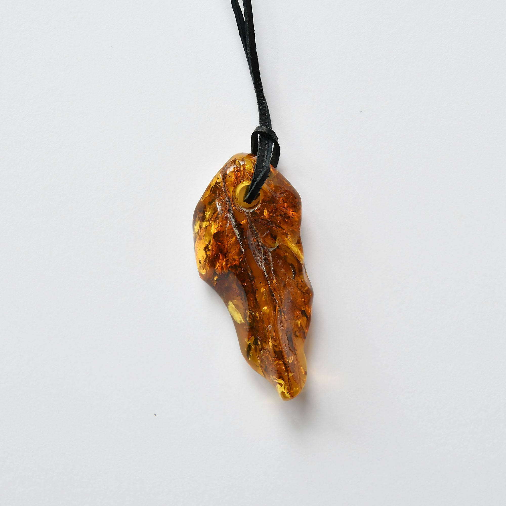 Amber amulet of brown pattern on a leather rope