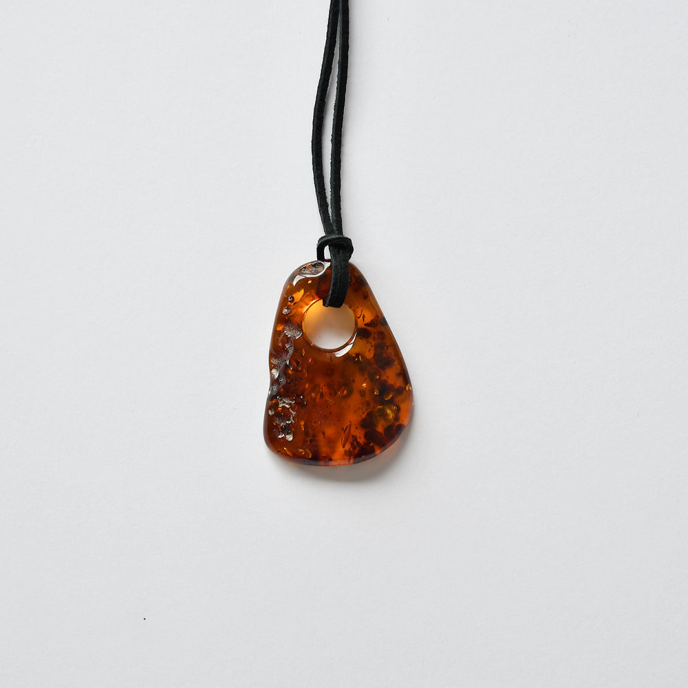 Amber amulet of cherry color and a large round hole