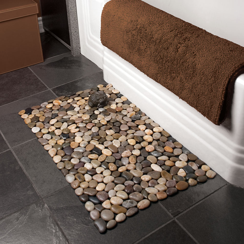 Bath mat with river rocks measuring 18 inches by 30 inches mounded on a mesh backing displayed over edge of bath tub with brown towel hanging.