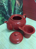 red ceramic teapot with lid off and ceramic infuser shown