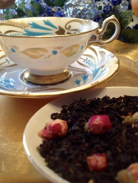 black tea with roses and teacup