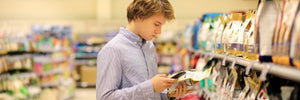 Young man studying pet food labels in a grocery store