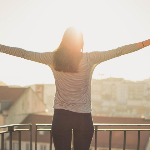 woman standing in morning sunshine with outstretched arms