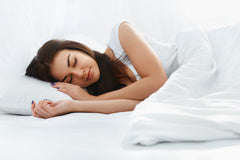 Woman resting in bed with alpaca quilt