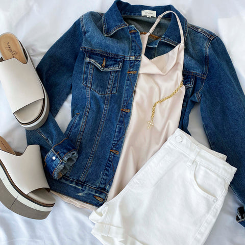 An outfit laid out including a denim jacket, tank top, white denim shorts and sandals