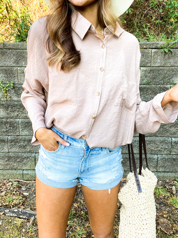 girl wearing a light brown button down with denim shorts and a hat