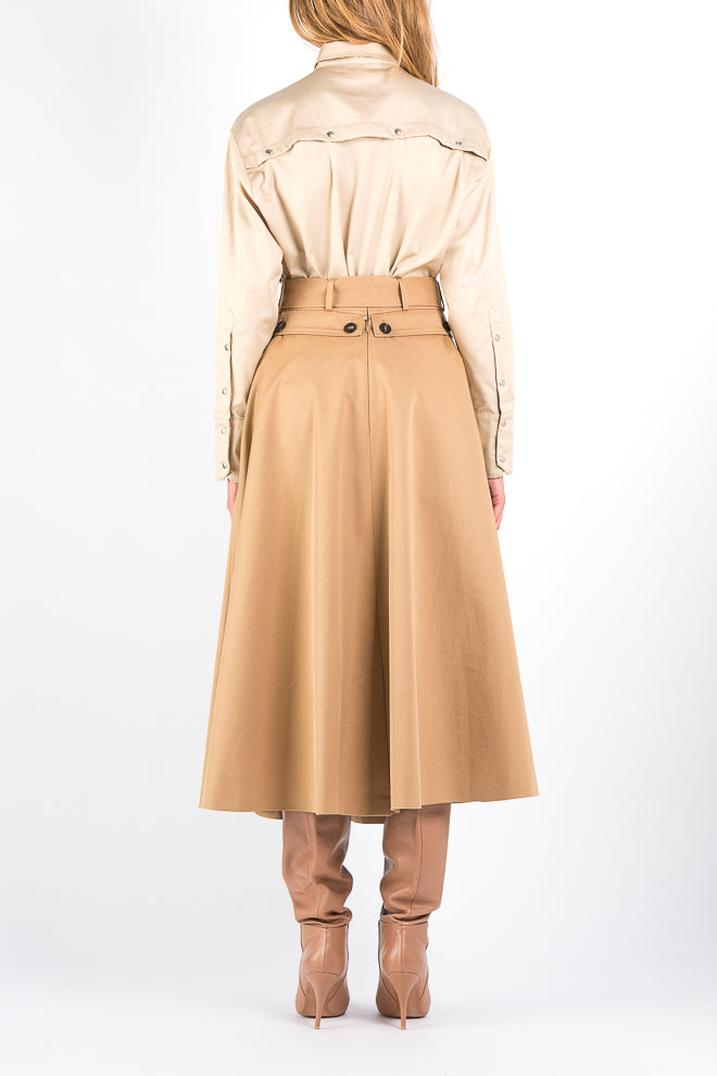Button Off | Skirt | Camel. Two midi skirts in one. Buttons at the waist so you can button off the upper layer and a second soft satin layer will appear. A skirt with possibilities. Model wears a size 36.