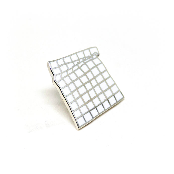 hard enamel pin, a 9x7 grid of squares curling folding near the top like cloth, silver outlines on white background