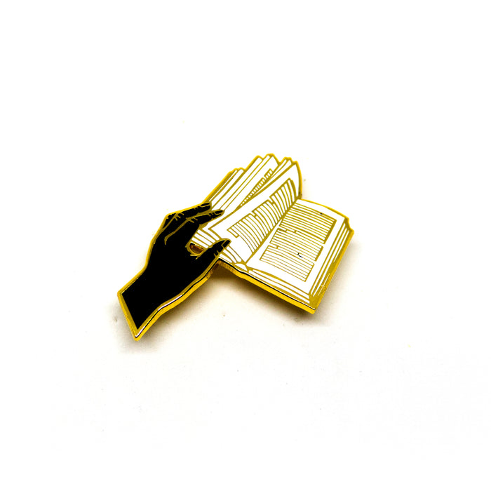 hard enamel pin, a hand holds open the pages of a book, the words in the book are represented by abstract, straight lines, gold outlines on black hand, white book