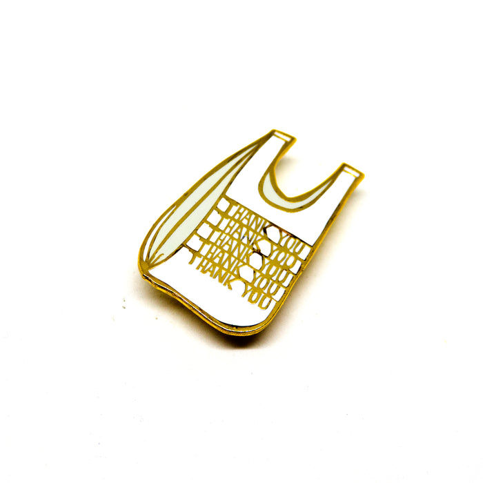 "hard enamel pin, plastic grocery bag with the words ""Thank You"" repeated vertically on it five times, gold outlines, white bag, light grey shadows"