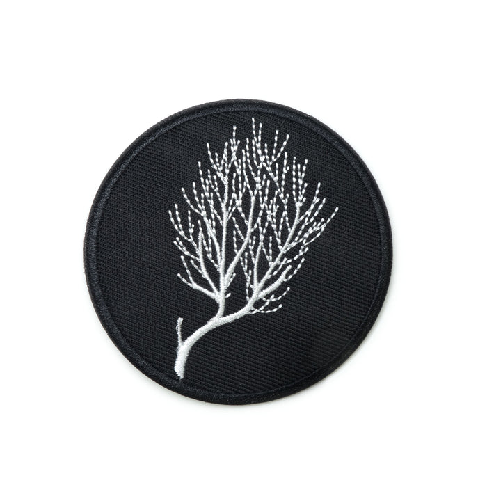 a circular patch, white embroidered lines linework of bare branches of a bush on black background
