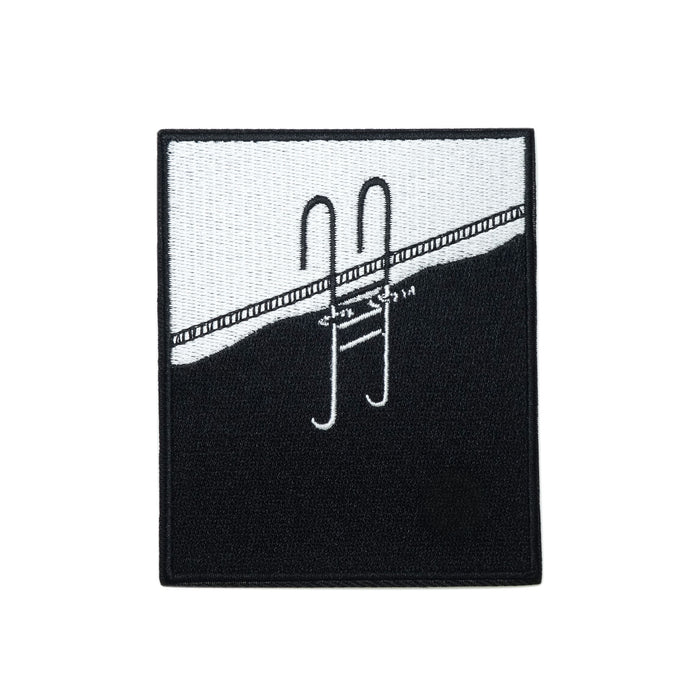 a rectangular embroidered patch in black and white, taller than it is wide, a pool ladder in black emerges out onto the edge of a swimming pool, the submerged portion of the ladder can be seen in white through the black water