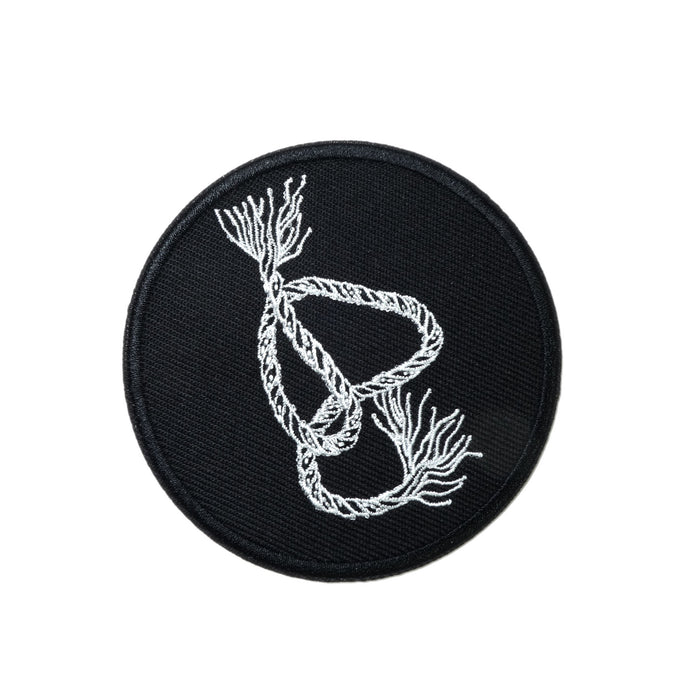 circular embroidered patch, white outlines of a snaking piece of braided rope with frayed ends on black background