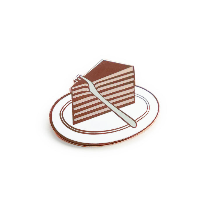 a hard enamel pin, grey fork cutting through a wedged slice of pink and copper layered cake on a white plate