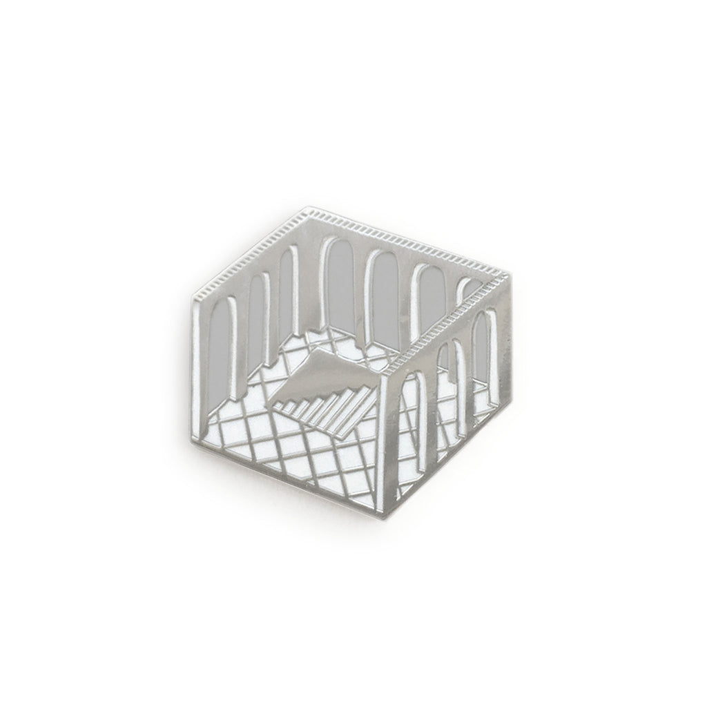 a highly reflective hard enamel pin, a diamond shaped cross-section of a room with no ceiling, arches cut into the walls, tiled floor, and a hole in the floor containing steps leading below, silver outlines, grey negative space for the arches, white tiles and highlights