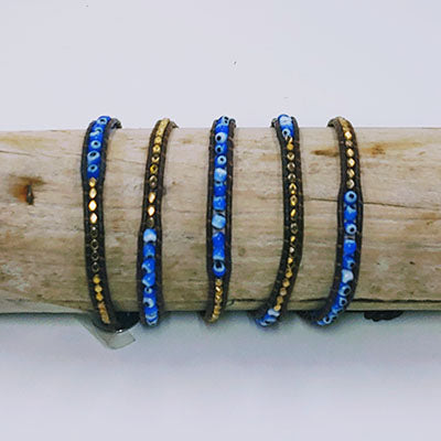 "Blue stone with black dots and gold colored metal pieces with leather strips. 36"" long."
