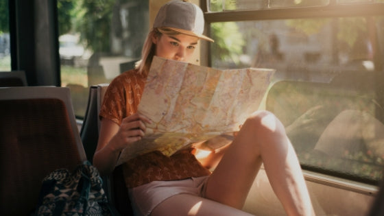 girl travelling on train with map safety tips