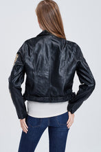 back view of faux leather jacket with embroidered sleeves. meets at your waist. zip up in front and tie around waist