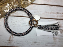 small print leopard animal print with white background bangle ring keychair with tassle and monogram tag. large ring for any size wrist and easy clip for attaching keys. contains two 2 rings to attach keys to. leopard print, animal print, cute, and fun.