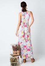 back view of pale mint and floral print pattern long maxi dress with sleeveless top. cinched at small of wasit and has pockets