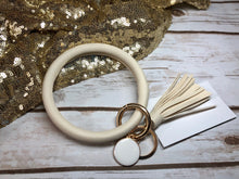 cream bangle ring keychair with tassle and monogram tag. large ring for any size wrist and easy clip for attaching keys. contains two 2 rings to attach keys to. monochromatic, cute, and fun.