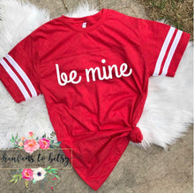 Red varsity short sleeve be mine t-shirt with be mine in white contrast on front middle of tee. Red and white contrast