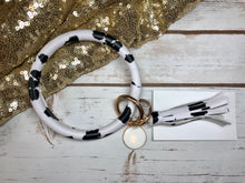 black and white cow print bangle ring keychair with tassle and monogram tag. large ring for any size wrist and easy clip for attaching keys. contains two 2 rings to attach keys to. cow print, animal print, cute, and fun.