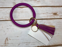 purple bangle ring keychair with tassle and monogram tag. large ring for any size wrist and easy clip for attaching keys. contains two 2 rings to attach keys to. monochromatic, cute, and fun.